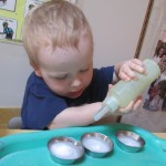 Picture of a Child squirting liquid from a bottle into metal dishes.