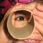 Picture of a child looking through a cardboard tube.